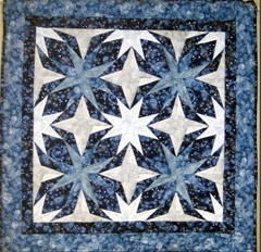 "This paper pieced wallhanging was made using Carol Doak's pattern ""Laurel"" from her book 40 Bright & Bold Stars.Top & backing are constructed using quality 100% cotton, batting is low loft polyester. Machine pieced and machine quilted by Linda Monasky."