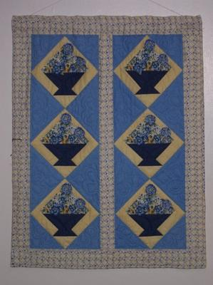 This wall hanging was made from an Elenor Burns pattern and 3D flowers are sewn on with sead beads .Top & backing are constructed using quality 100% cotton, batting is low loft polyester. Machine pieced and machine quilted by Linda Monasky.