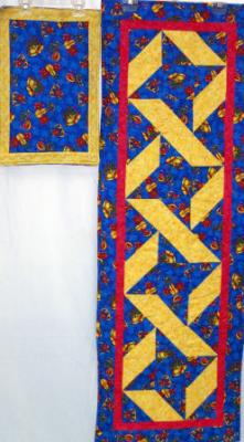 Christmas table runner (no placemats)gold and blue cotton prints, machine pieced by Margaret Sudbey and machine quilted by Linda Monasky.    <br />