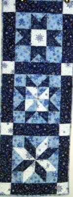 3 different star patterns give this table runner more interest.All fabrics are quality 100% cotton winter prints. Machine pieced and machine quilted by Linda Monasky.<br />