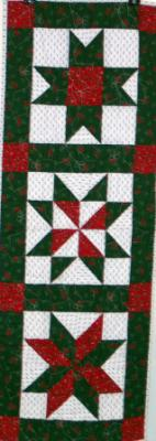 Red green $ white Christmas prints in 3 different star patterns give this table runner more interest. Machine pieced and machine quilted by Linda Monasky.<br />